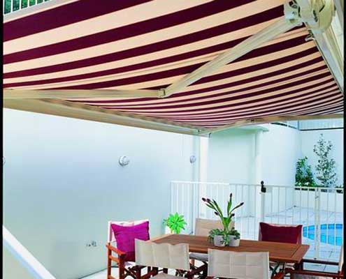 Pool side dining under an expansive folding arm awning