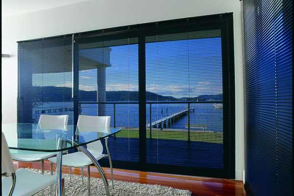 Dark aluminium venetian blinds with view out to the river.