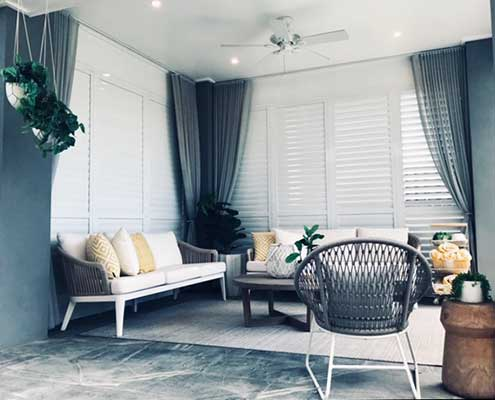 Blue grey sheer curtains complemented with shutters for a hamptons effect.