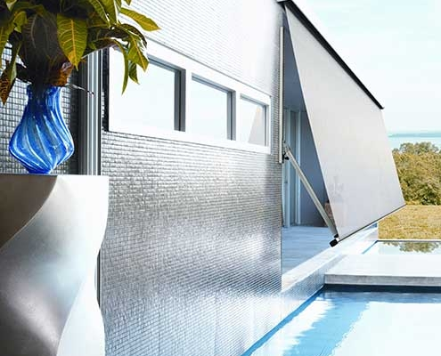 Grey pivot arm awning provides protection from the UV, wind and rain