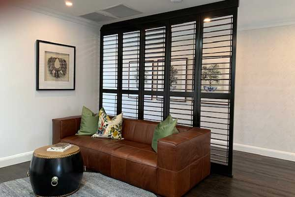 Chic black shutters used for a room divider or wall replacement