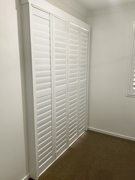 White Shutters in a bedroom in Bundaberg wth brown carpet delivered as bifold on a sliding screen.